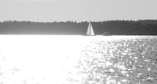 Likt segelbåten som glider igenom solens glittrande ljus mot den skuggiga sidan. Det är som livet ljusa och mörkare dagar, men alla dessa dagar ingår i livets seglats.