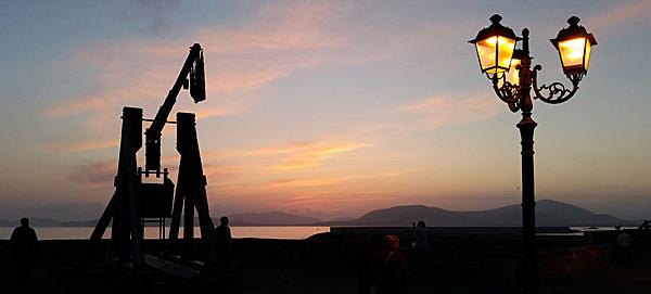 Livets eget yin & yang! En vy av jordens vackraste solnedgång som ses från en mur byggd för krig och förödelse.
